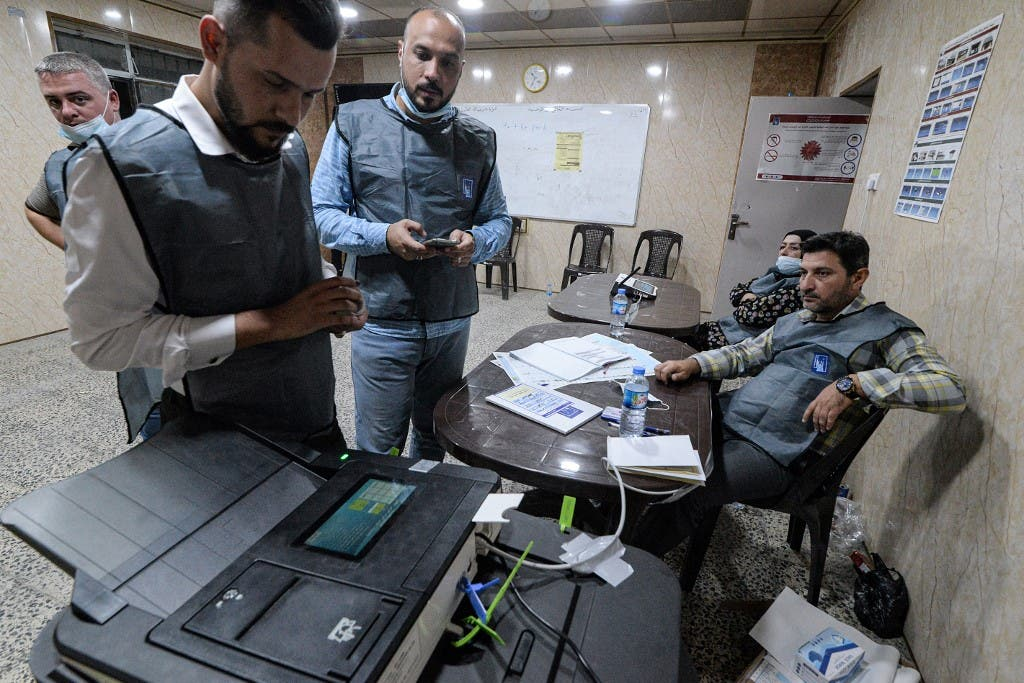 Iraqi election officials conduct an electronic ballot count at a polling station in Mosul